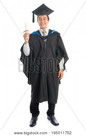 Full body male university student in graduation gown holding paper certificate, standing isolated on white background. Attractive Southeast Asian model.