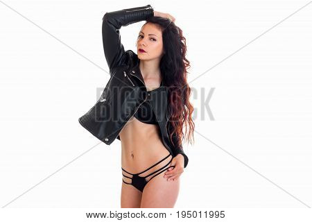 erotic young brunette in black lingerie and leather jacket stands in front of a camera isolated on white background