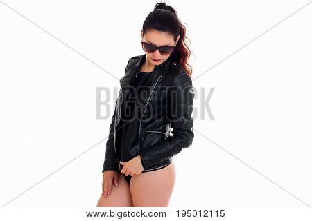 young gorgeous brunette in glasses and a black jacket posing in Studio isolated on white background