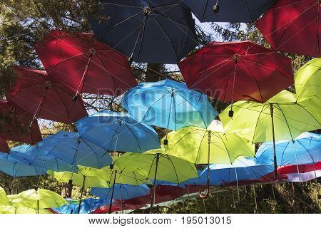 Colorful umbrellas background. Colorful umbrellas urban street decoration. Hanging Multicoloured umbrellas over blue sky. Abstract color background
