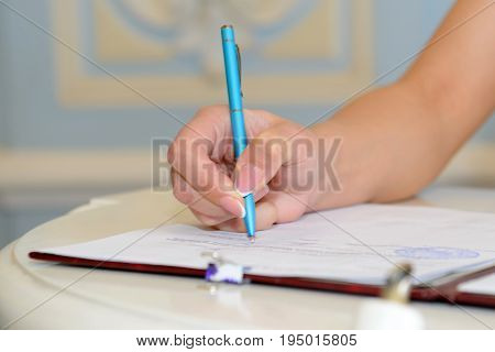 Woman's hand signing a contract. Signed an official document with a pen and paper.
