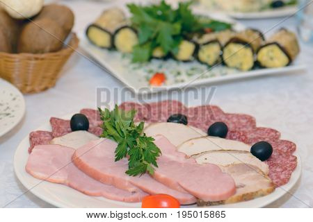 Cold meat appetizer - a dish with sausage and ham on the holiday table. Food ham diner.
