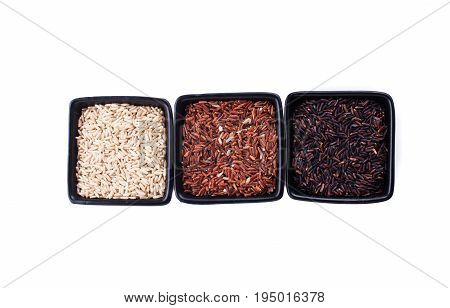 Various types of non-white rice in black bowls isolated on white