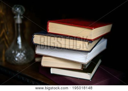 Paper book in a pile and a carafe of alcohol on the shelf intellectual. Education and intelligence are well-read people. Old gadgets from short stories and novels. The passing of time read.