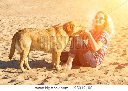 Portrait of young beautiful woman in sunglasses sitting on sand beach hugging golden retriever dog. Girl with dog by sea. Happiness and friendship. Pet and woman.woman playing with dog on sea shore. Sun flare