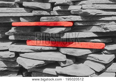 Two red stones among the gray stones which are stacked one on the other.