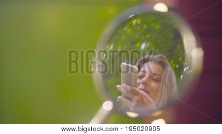 Close up portrait of young woman with smartphone reflection in the rear view mirror of the scooter