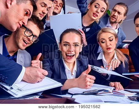 Business people office life of team people working with papers sitting table . Woman and men show gesture thumb up.