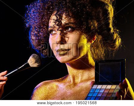 Visagiste woman with decorative cosmetics. Girl with curls holds eye shadow and brush on dark background. Golden powder on female bare shoulders on black background. Master class make-up.