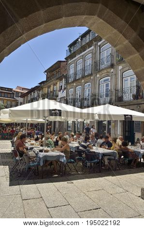 GUIMARAES, PORTUGAL - AUGUST 9, 2015: People at outdoors restaurant in plaza in the old town of Guimaraes Portugal.