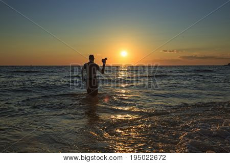 man with a camera walks into the sea at sunset.  professional photographer goes on water to take a photo of the ocean