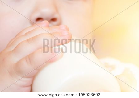 Feeding the baby is holding a bottle of milk by hand. Close up