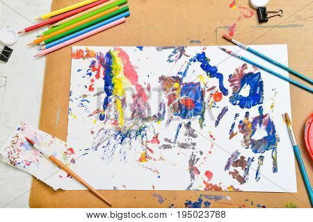 Poster color art on white sketch paper with pencils painting brush colour tray of white yellow blue red green and black clips over cork board background