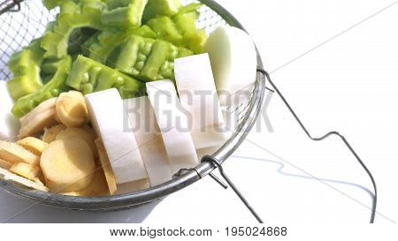 Chinese radish with Gourd and Ginger are raw herb for cooking the chicken soup In a sieve on white background Photo close up at Chinese radish and has copy space.