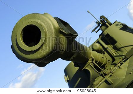 Cannon barrel of powerful green tank with blue sky on background, modern army artillery, military industry, selective focus