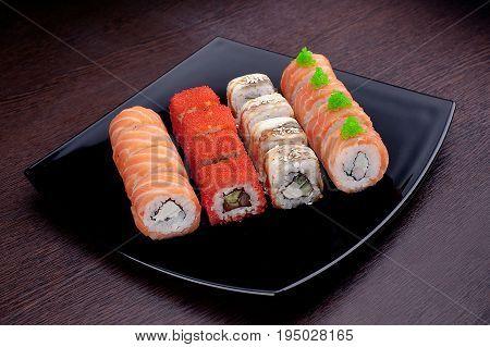 Set of sushi maki on black plate. Japanese food isolated on background