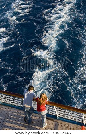 Young couple on the stern of a cruise ship.