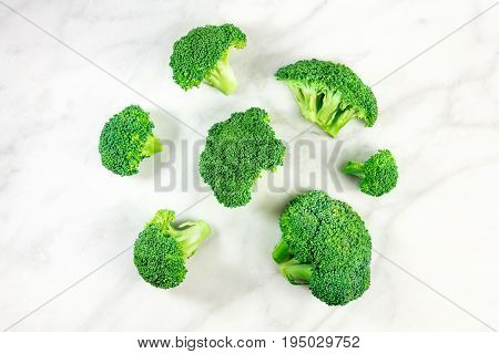 Vibrant green broccoli florets, shot from above on a white marble texture with a place for text