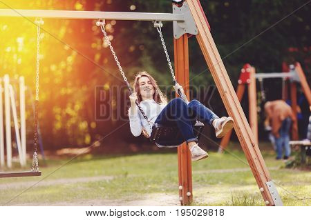 Girl student, teenager is smiling and swinging on a chain swing in the park. Concept is a playground for rest and a happy vacation in a new place. Shine of the sun.