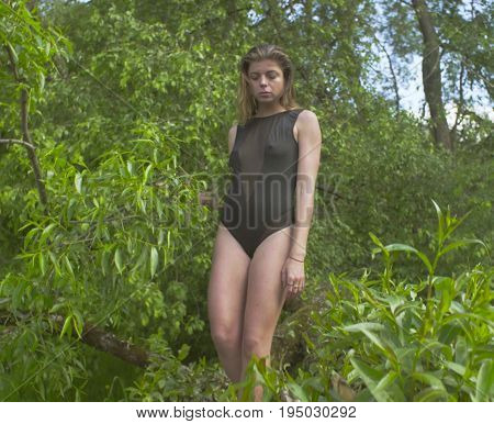 Young woman in a black bathing suit walking on a tree branch over a river. Then lies down on it.