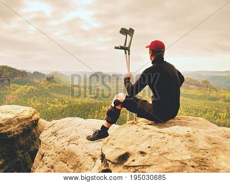 Tired Tourist With Medicine Crutch  And Broken Leg Fixed In Immobilizer Resting On  Mountain Summit