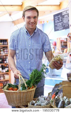 Male Shopper In Delicatessen Buying Organic Produce