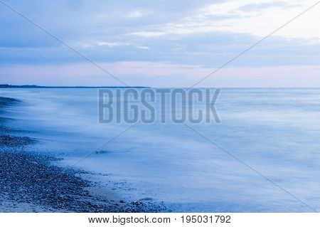Moody empty sea and beach at dusk pebbles on beach pastel pink and blue sky tranquility and peace scene
