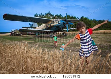 Kids are playing nearby to the agricultural airplane.