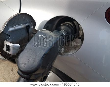 gas nozzle in small silver or gray car when pumping gas