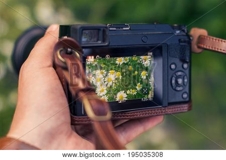 DSLR camera in hand shooting in the hands of a man. The camera shows flowers