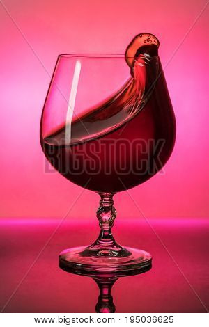 Red wine in a glass splashes out, shot at the light, close-up