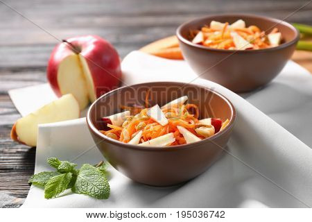 Clay bowls with yummy carrot raisin salad with apple on kitchen table