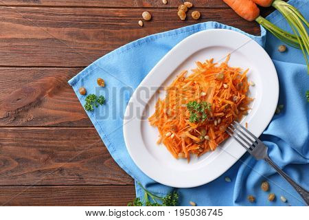 White plate with yummy carrot raisin salad on cute blue napkin, top view