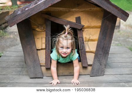 Small laughing girl protrudes from the window of a small wooden house