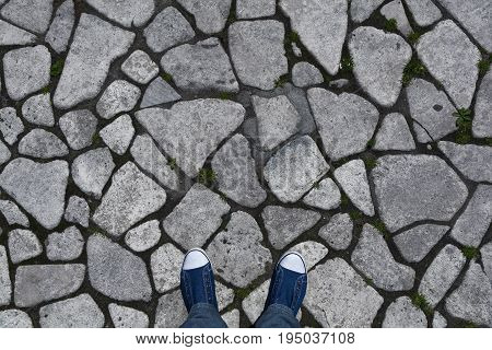 Background, texture of rough stone on the pavement. The legs in the sneakers are a top view. Empty space, space for text, abstract grey background