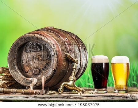 Glasses of  beer and ale barrel on the wooden table. Craft brewery. Sunny summer background.