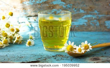 glass of herbal chamomile tea and linden honey on a blue wooden table. Chamomile tea in a transparent cup and camomile flowers on wooden table. Herbal tea for baby's stomach. Copyspace.