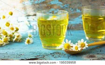 two glasses of herbal chamomile tea on a blue wooden table. Chamomile tea in a transparent cup and camomile flowers on wooden table. Herbal tea for baby's stomach. Copyspace.