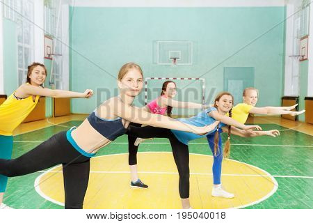 Group of teenage girls in sportswear holding balance, standing on one leg in sports hall