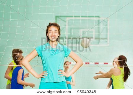 Close-up portrait of Asian teen girl standing next to the volleyball net with arms at hips