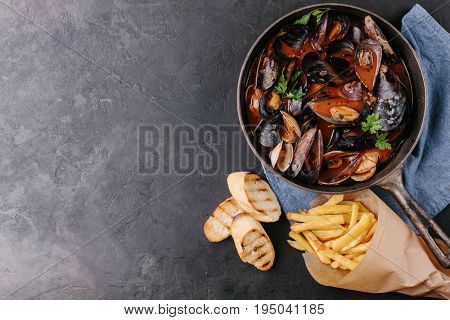 Mussels in a frying pan in tomato sauce, French fries and croutons on a dark background. Top view. Copy space.