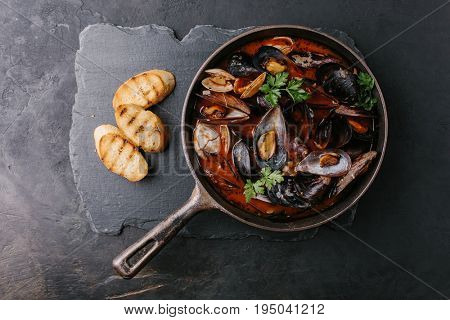 Mussels in a frying pan in tomato sauce and croutons on a stone plate. Top view.