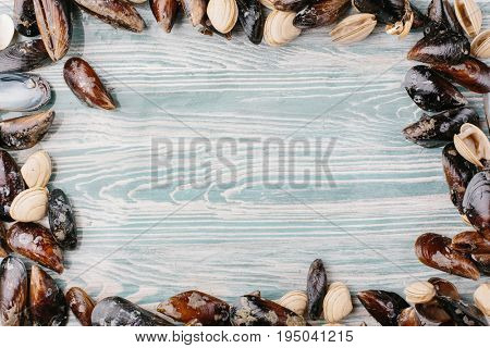Fresh seafood. Clams and mussels over a wooden background. Food frame.