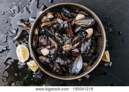 Mussels in a metal plate with ice and lemon over a stone background. Top view.