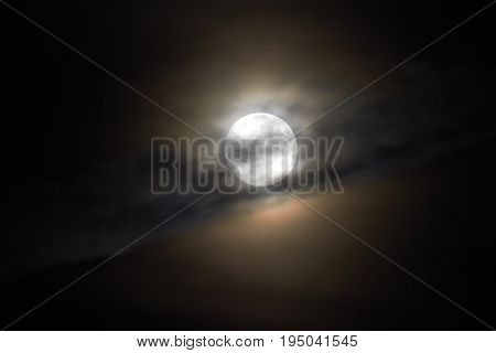 The moon appears in the night behind a cloud.