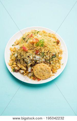 Bhel Puri - Popular Mumbai street food served with coriander and tamarind chutney on white background, selective focus