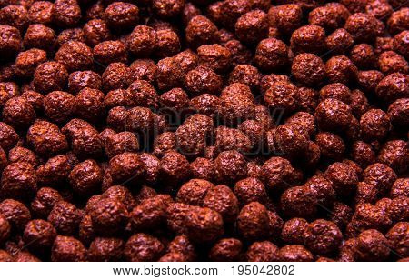 Chocolate breakfast cereal texture. Cereal balls as background. Chocolate corn balls wallpaper background cover.