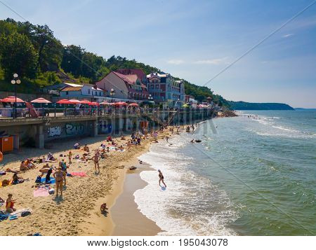 Svetlogorsk - Russia, July 12, 2017: People relax and sunbathing at Baltic Sea shore at sunny summer day