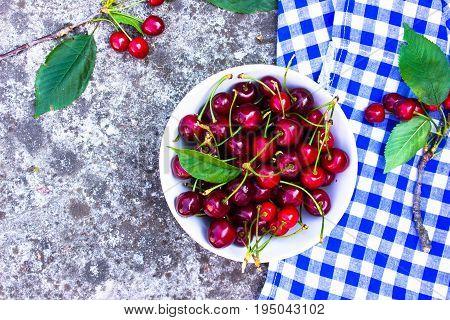 red ripe fresh cherries in bowl on concrete background. Garden fresh organic cherries . Food background. cherries/ cherries