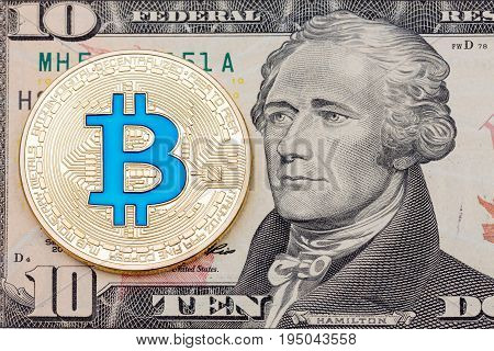 Golden cryptocurrency blue bitcoin on ten dollar banknote background. High resolution photo.